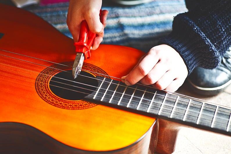 Bei einer klassischen Gitarre neue Saiten aufziehen